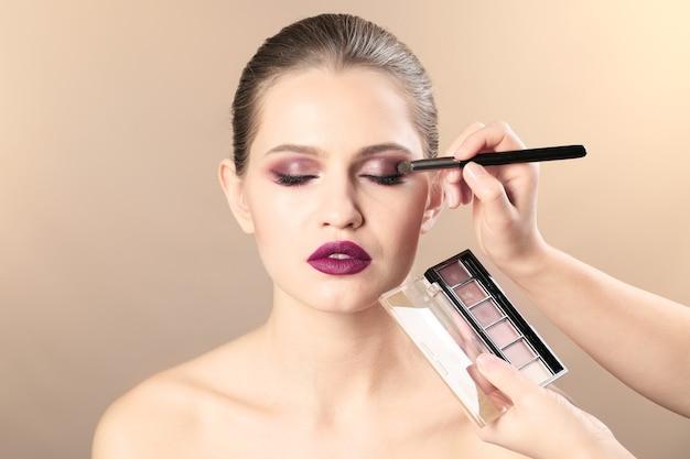 Professionele gezichtskunstenaar die make-up op het gezicht van de vrouw op beige toepast