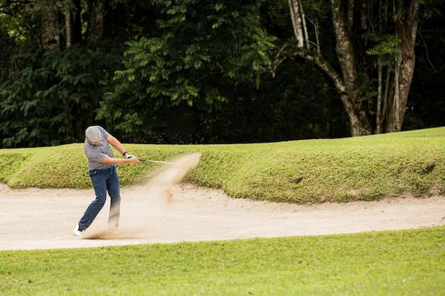 Professionele golfer. raakt de bal uit de zandbak. bali. inodesie.
