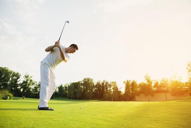 Professionele golfer taking swing shot op koers.