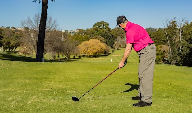 Professionele golfspeler die met een golfclub speelt op de met gras begroeide baan