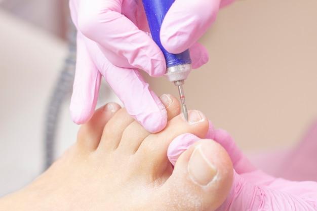 Professionele hardware pedicure met behulp van een elektrische machine. patiënt bij de pedicureprocedure. het polijsten van de nagelplaat, het verwerken van de nagelriem met een pedicuremachine.