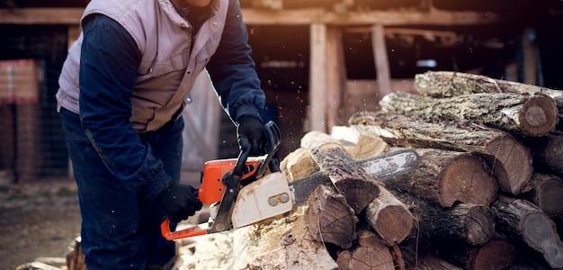 Professionele houthakker die boom snijdt die beschermende kleding draagt die een kettingzaag gebruikt.