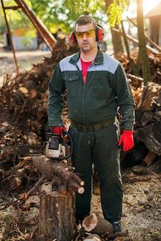 Professionele houthakker die zich met kettingzaag bevindt en de camera bekijkt terwijl het hebben van een onderbreking.