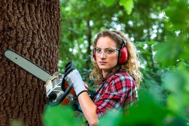 Professionele houthakker in het bos die een eikenboomstam met kettingzaag snijdt