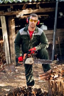 Professionele houthakker met bril en oorbescherming met kettingzaag