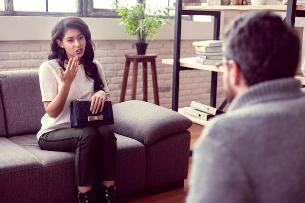 Professionele hulp. leuke, aangename vrouw die met haar therapeut praat terwijl ze haar problemen met hem deelt