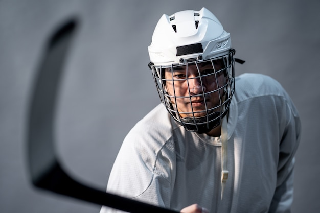 Professionele ijshockeyspeler voel boos, één verlichting in een donkere kamer.