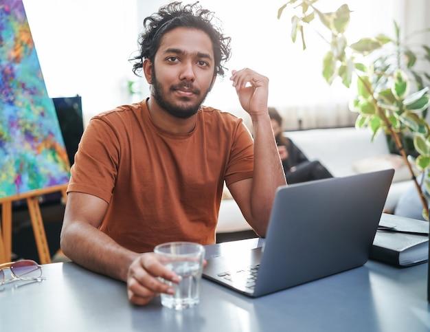 Professionele indiase kantoormedewerker met laptop zit aan tafel, er zijn desktopcomputer en kopje water overdag op kantoor.