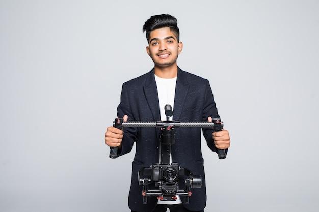 Professionele indiase man videograaf met gimball video slr ronin geïsoleerd op studio achtergrond