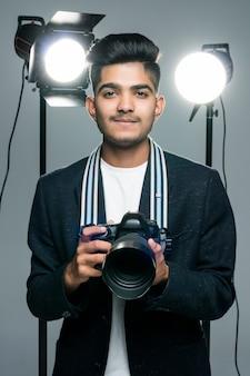 Professionele indische jonge fotograaf die foto's in studio met licht maakt
