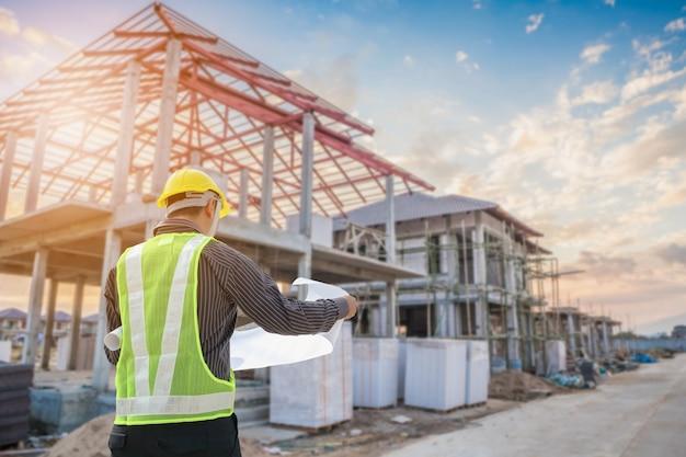 Professionele ingenieur architect werknemer met beschermende helm en blauwdrukken papier bij woningbouw bouw site achtergrond