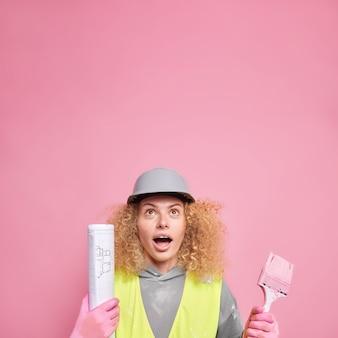 Professionele ingenieur in veiligheidskleding boven gericht met verbaasde uitdrukking houdt de mond open van verwondering houdt blauwdruk panintborstel staat tegen roze muur lege ruimte. industrieel