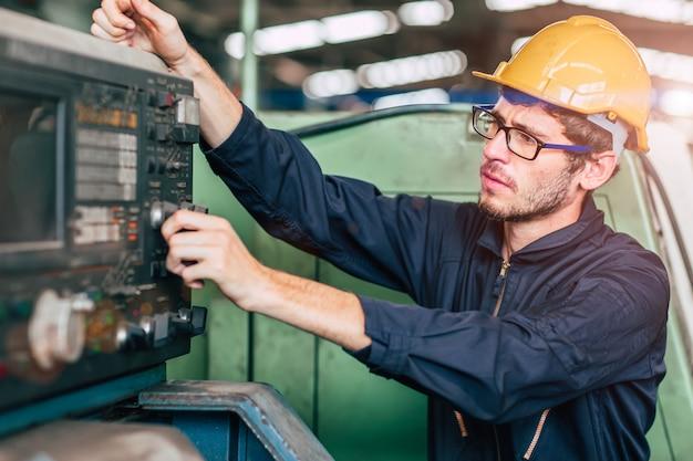 Professionele jonge arbeidersbril, ingenieur bij cnc het controlebord van de machinebediening draagt veiligheidspak