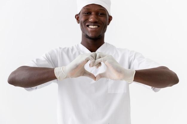 Professionele jonge arts die een hartvorm maakt