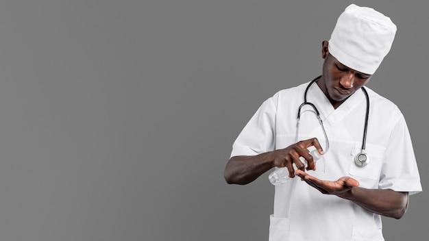 Professionele jonge arts die handdesinfecterend middel gebruikt