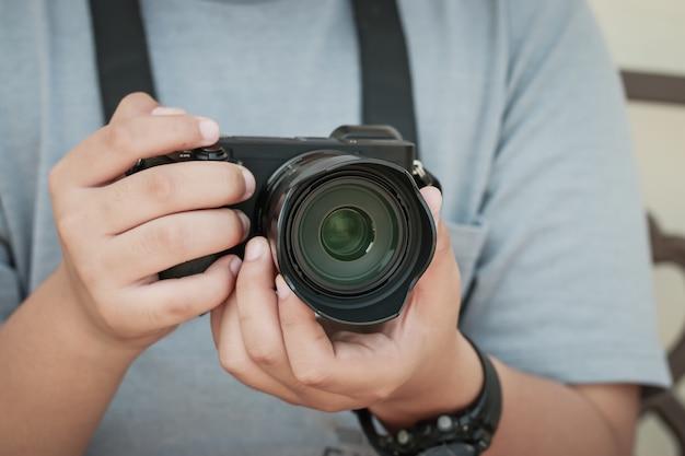 Professionele jonge fotograaf die werkt concentraat past nieuwe spiegelloze camera aan voordat hij gaat fotograferen of foto's maakt, lensfocus. hobby creatief apparatuurconcept