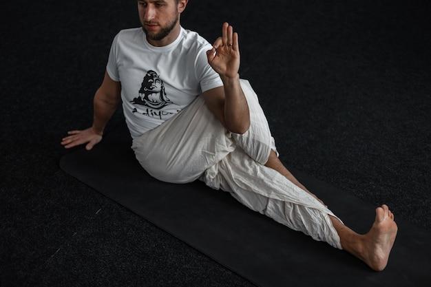 Professionele jonge man doet yoga op mat binnenshuis. trainer rekt zich uit en laat goed zien.