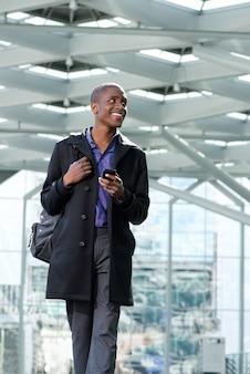 Professionele jonge man lopen met mobiele telefoon op het station