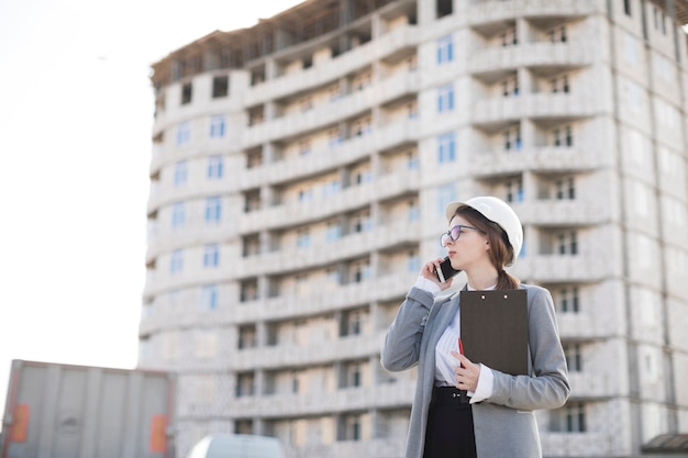 Professionele jonge vrouwelijke architect die op het klembord van de cellphoneholding bij bouwwerf spreekt