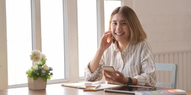 Professionele jonge vrouwelijke ontwerper die aan haar project met digitale tablet werkt