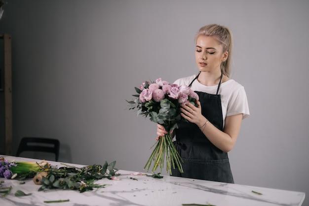 Professionele jonge vrouwenbloemist die schort draagt die bloemensamenstelling van verse rozen maakt