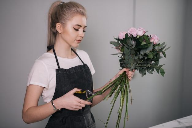 Professionele jonge vrouwenbloemist die schort draagt die stengel van bloemen met een schaar snoeit