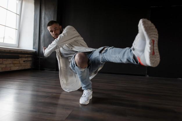Professionele jongeman danser in stijlvolle mode kleding met gescheurde spijkerbroek en schoenen die presteren in een donkere dansstudio