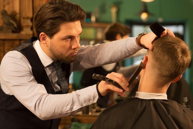 Professionele kapper die bij zijn herenkapper werkt