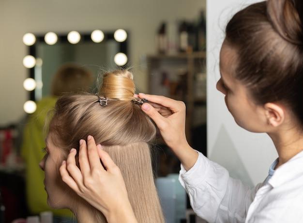 Professionele kapper die het haar fixeert en voorbereidt voor het stylen