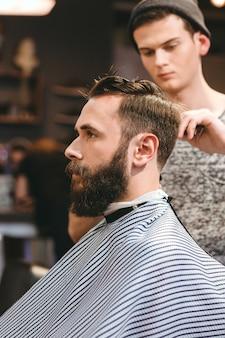 Professionele kapper die het haar van een jonge, bebaarde man in de kapsalon knippen
