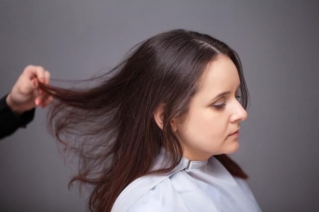Professionele kapper die met jonge vrouw in schoonheidssalon werkt.