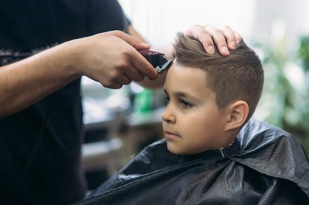 Professionele kapper gebruikt een tondeuse om haar te franjes voor een kleine jongen