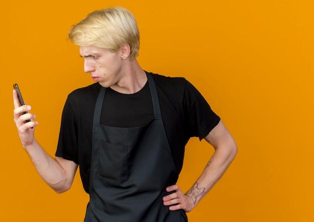 Professionele kapper man in schort kijken naar zijn smartphonescherm met ernstig gezicht ontevreden over oranje muur staan
