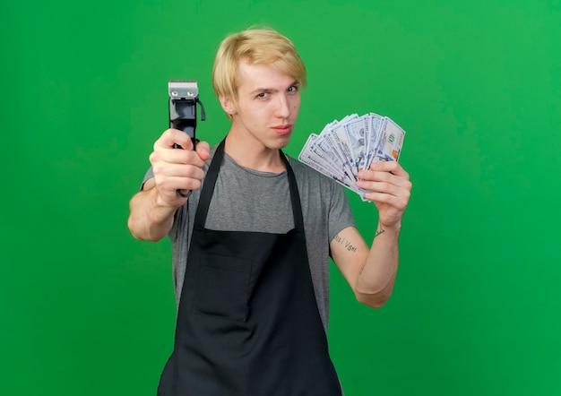 Professionele kapper man in schort met contant geld tonen trimmer op zoek zelfverzekerd