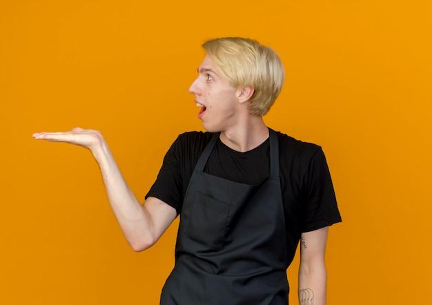 Professionele kapper man in schort op zoek opzij glimlachend presenterende kopieerruimte met arm van de hand staand