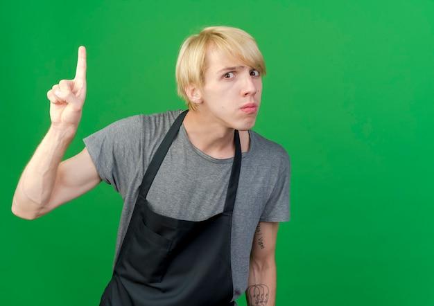 Professionele kapper man in schort wijsvinger waarschuwingsgebaar tonen