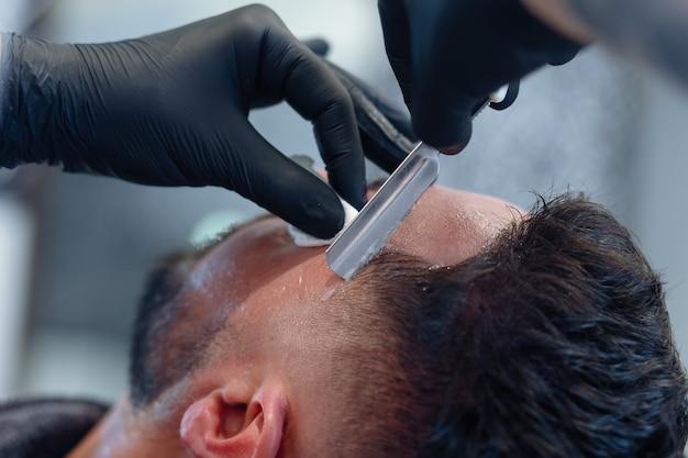 Professionele kapper scheert de baard van de klant met een scheermes. baard knippen met ouderwets mes bij kapperszaak. knappe macho man krijgt zijn baard geschoren in studio. close-up shot.