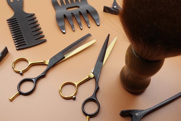 Professionele kappers tools geïsoleerd op bruine achtergrond kappers schaar kam en haarspeld