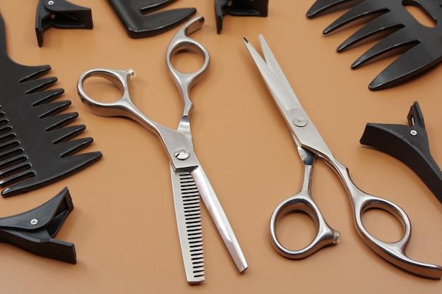 Professionele kappers tools geïsoleerd op bruine achtergrond kappers schaar kam en haarspelden