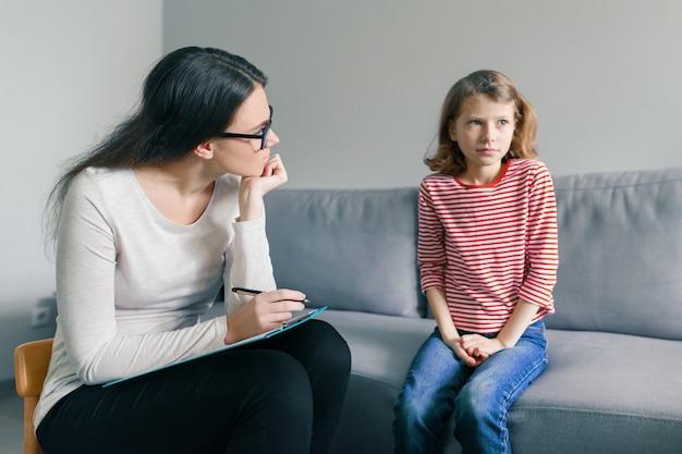 Professionele kinderpsycholoog die met kindmeisje spreekt in bureau