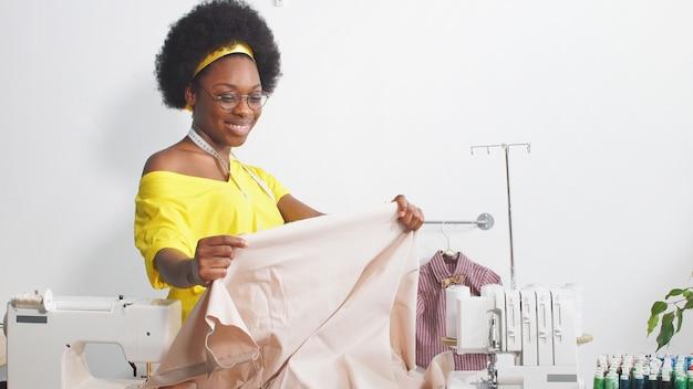 Professionele kleermaker afro-amerikaanse vrouw ontwerpt kleding in het atelier van de ontwerper