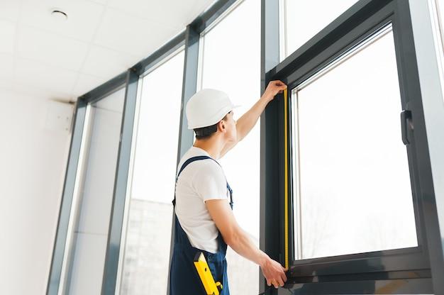 Professionele klusjesman die venster thuis installeert