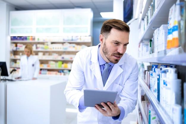 Professionele knappe mannelijke apotheker in witte jas tablet houden en kijken naar medicijnen in apotheek winkel of drogisterij.