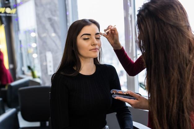 Professionele kunstenaar deed make-up poeder op model in zwarte trui