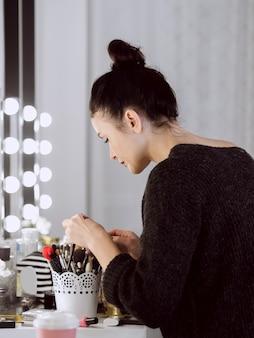 Professionele kunstenaar die make-upborstels bekijkt