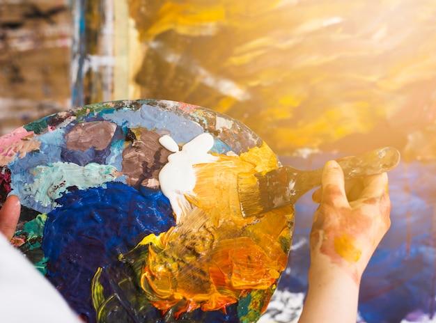 Professionele kunstenaar die olieverf met borstel op palet mengt