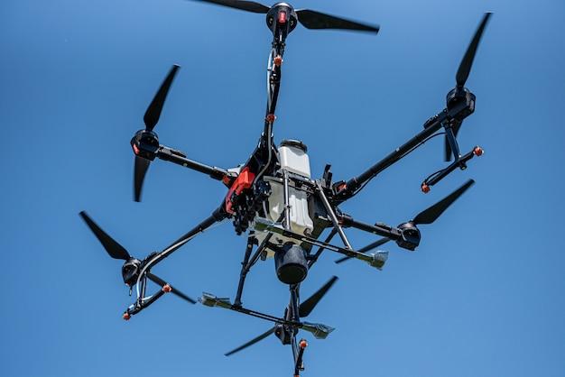 Professionele landbouwdrone die in de blauwe lucht vliegt