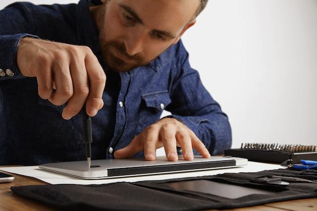 Professionele losdraaiende behuizing van metalen dunne laptop in zijn elektrische servicelaboratorium om hem schoon te maken en te repareren