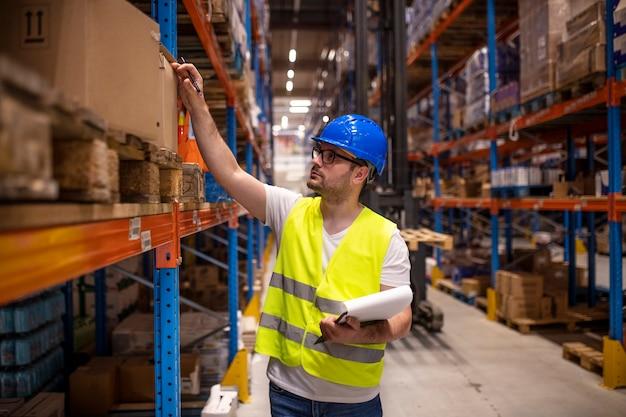 Professionele magazijnmedewerker in beschermende werkkleding checklist te houden en inventaris in opslagruimte te controleren