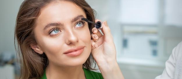 Professionele make-up artiest mascara toe te passen op de wimpers van mooie jonge blanke vrouw in de schoonheidssalon